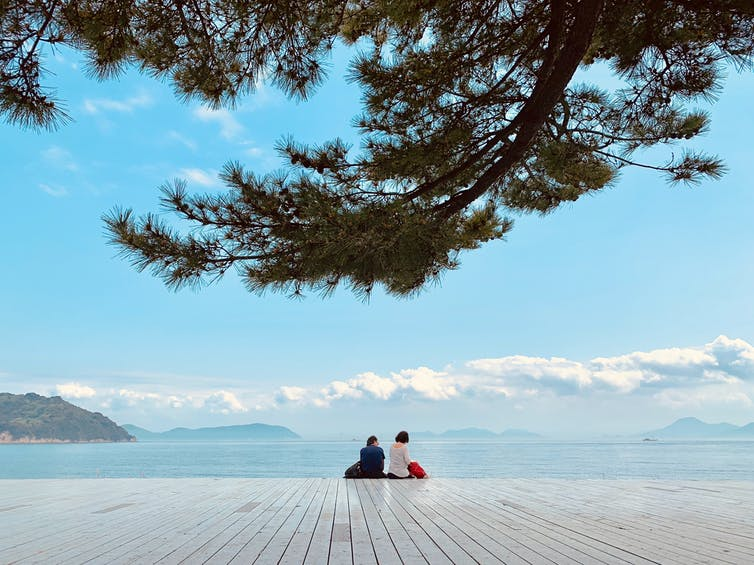 Couple sit on deck with Japan sea on horizon.